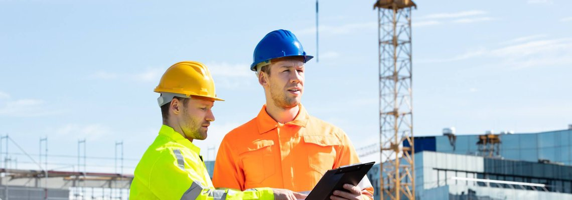 Two construction workers looking over a clipboard