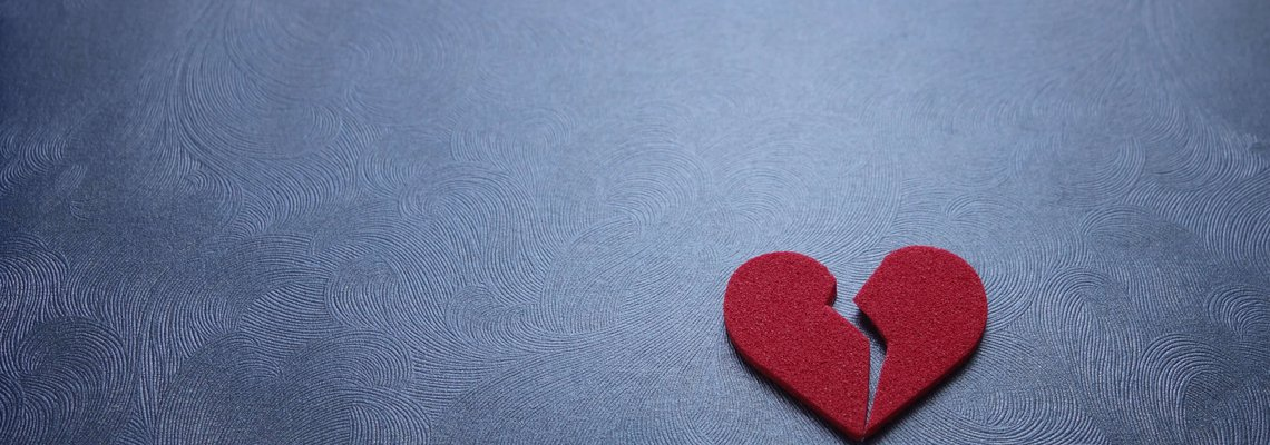 A red paper heart broken in half lying on a table.jpeg