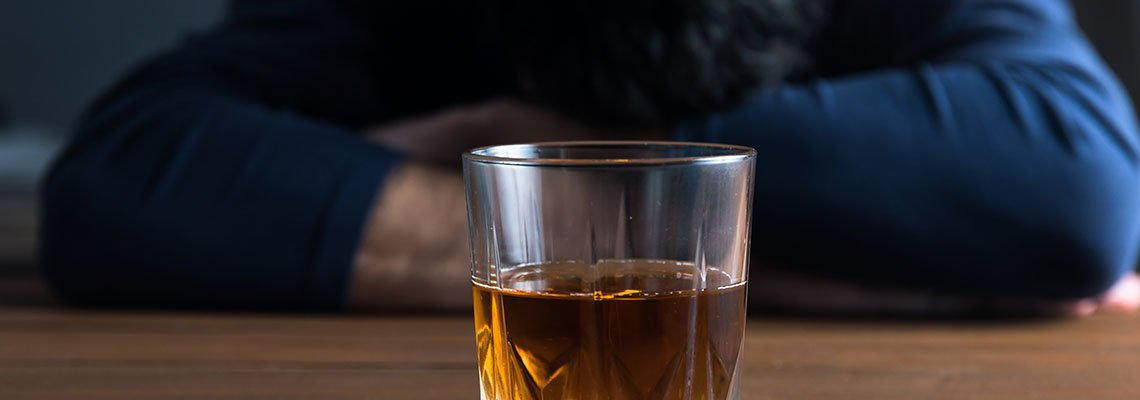Drink in Front of Person with Head Down