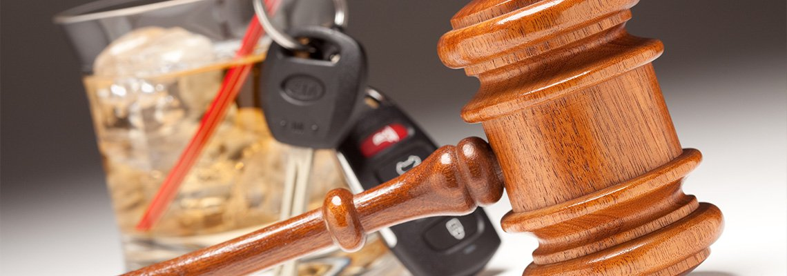 Gavel in Front of Drink with Keys on Straw