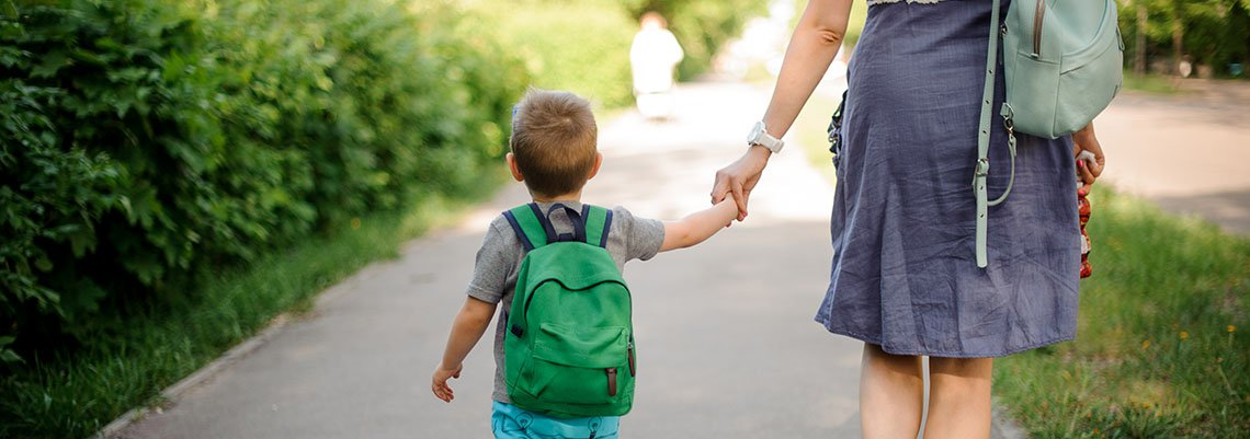 woman walking down a path with a little boy holding her hand