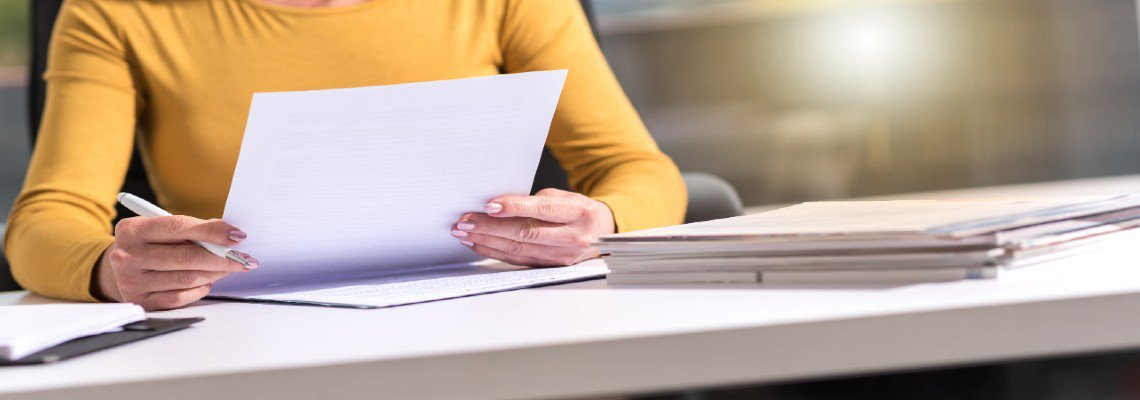Woman holding a pen and reading documents