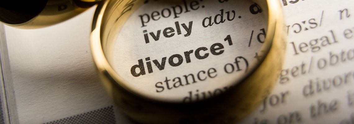 Gold ring highlighting the word divorce in a dictionary