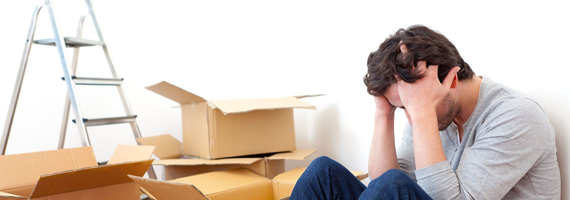 Man sitting with head in hands surrounded by boxes