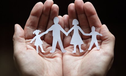 hands holding a paper cutout of family