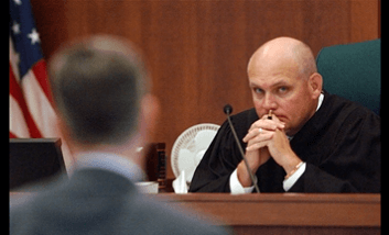 judge staring at person in suit