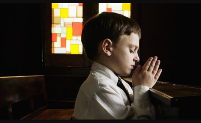Kid folding his hands praying
