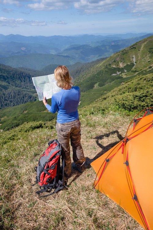 woman holding a map facing a valley