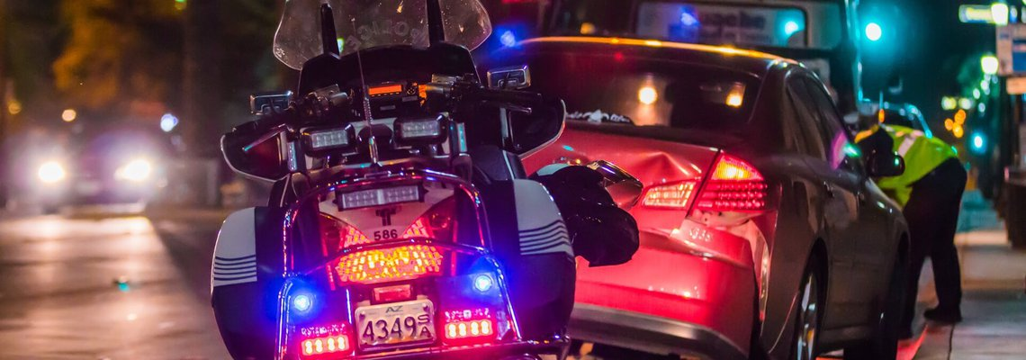 Police bike pulled up to a car accident scene at night