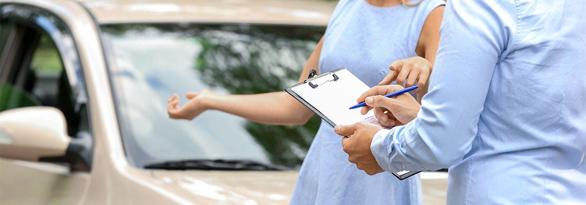 Man writing on a clipboard while woman explains car damage