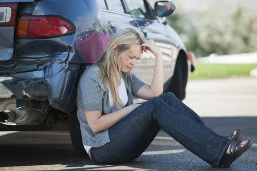 woman sitting next to a dented car