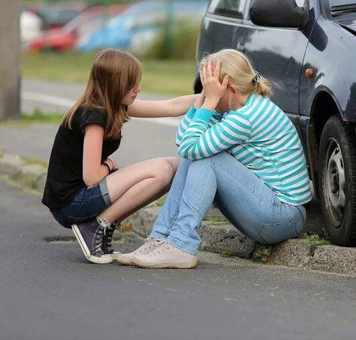 woman and daughter talking by car accident