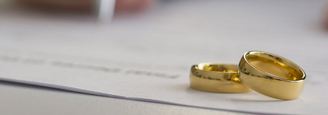 Rings resting on a document as a man signs at the bottom