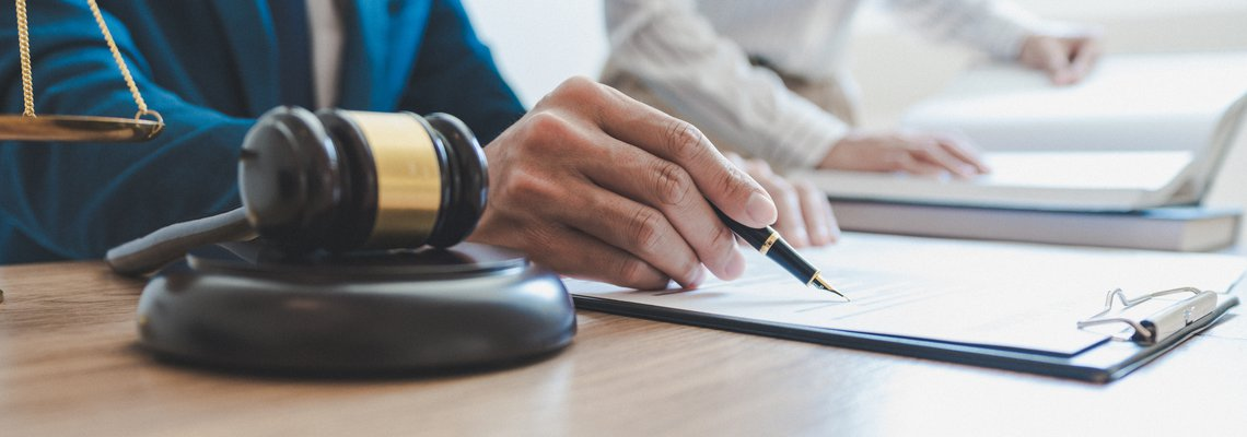 Man using pen to point at writing on a document and a gavel on the table