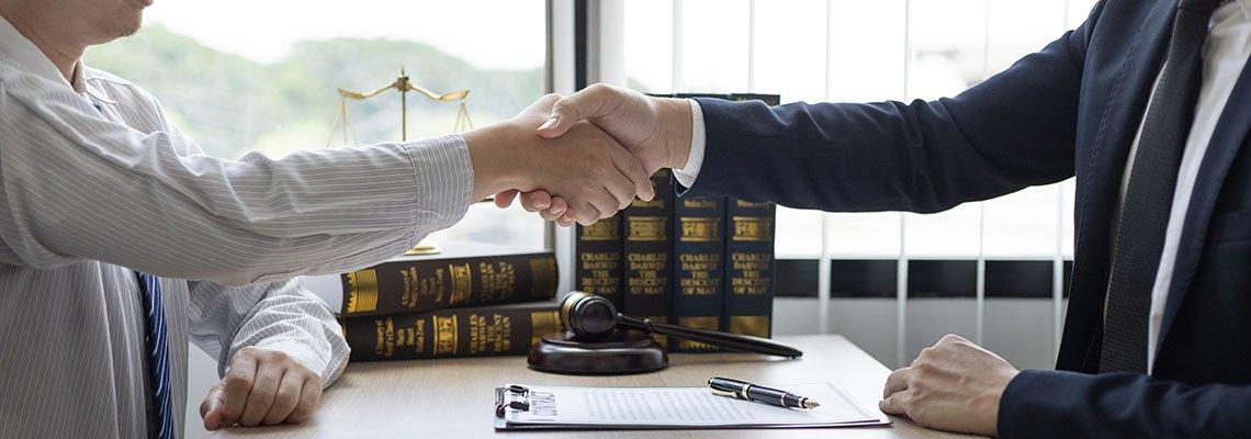 Two men shaking hands over a desk