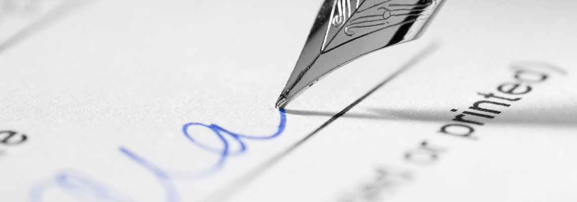 Pen signing a signature in blue ink on a document
