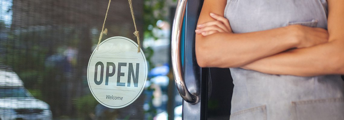 A woman standing in the door of an open business