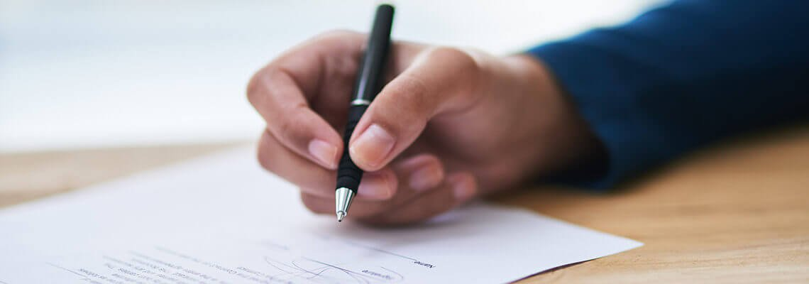 Hand holding a pen to sign a document