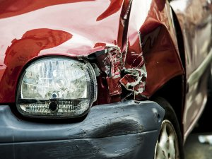 Close-up photo of a red car with a smashed headlight