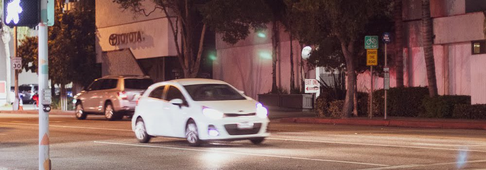 White car sitting at an intersection at night