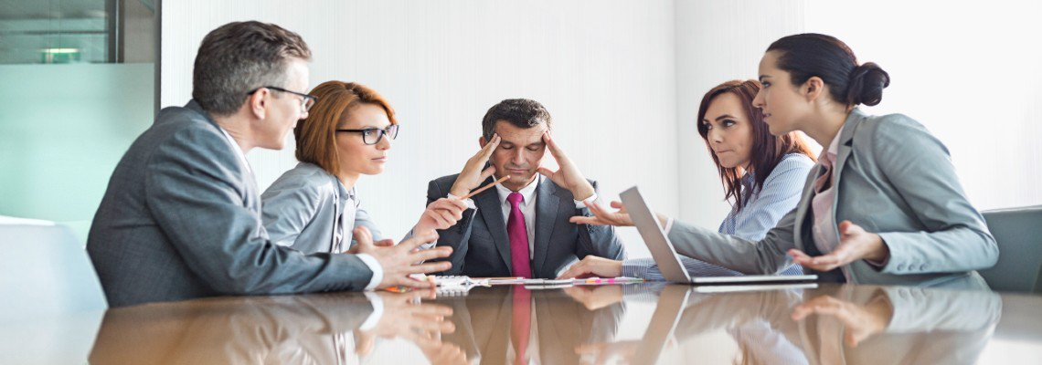 Man holding his head while business partners argue