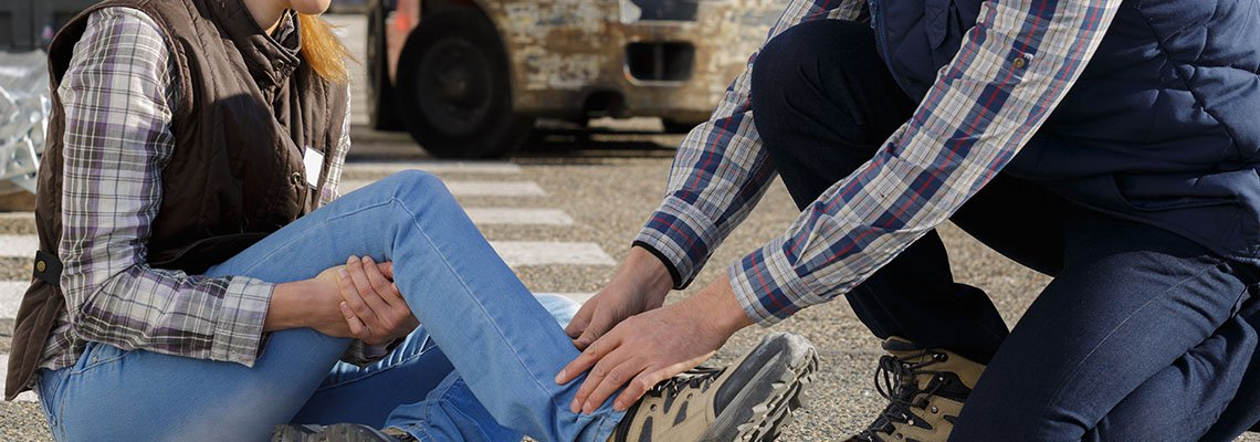 A man tends to an injured woman's ankle on a job site
