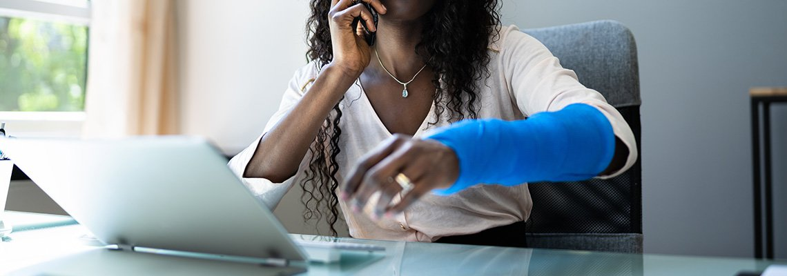 A woman holds her arm cast up while on the phone