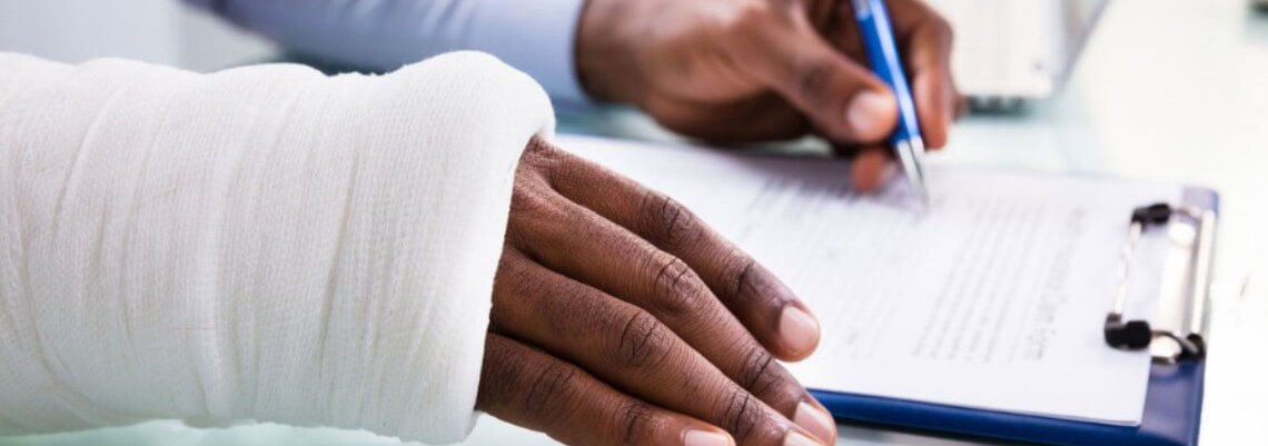 Injured person filling out paperwork with non-injured hand