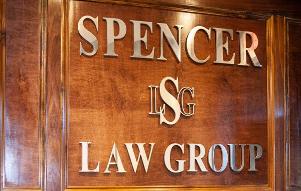 Wall with gold lettering on it reading Spencer Law Group