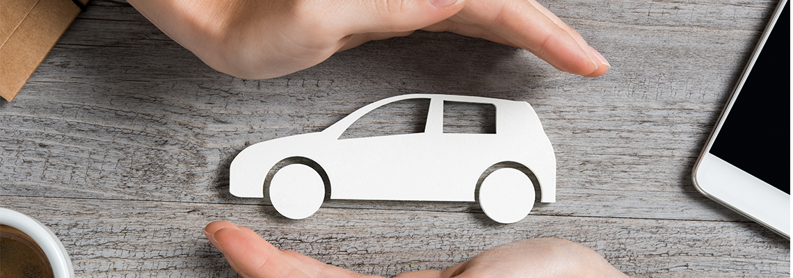 A paper car with hands around it