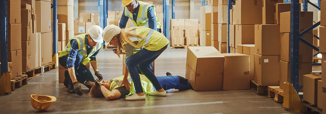 Worker hurt on ground surrounded by coworkers