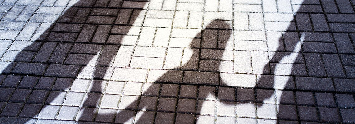 Shadows of a child holding hands with 2 adults