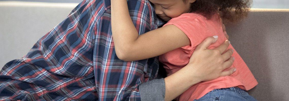 An adult hugging a little girl