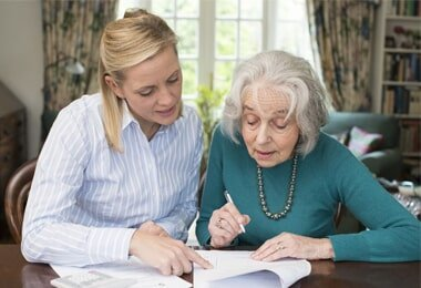 Elder Law — Woman Helping Senior with Paperwork in Independence, MO