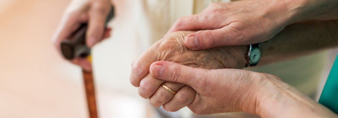 Person holding an elderly woman's hand