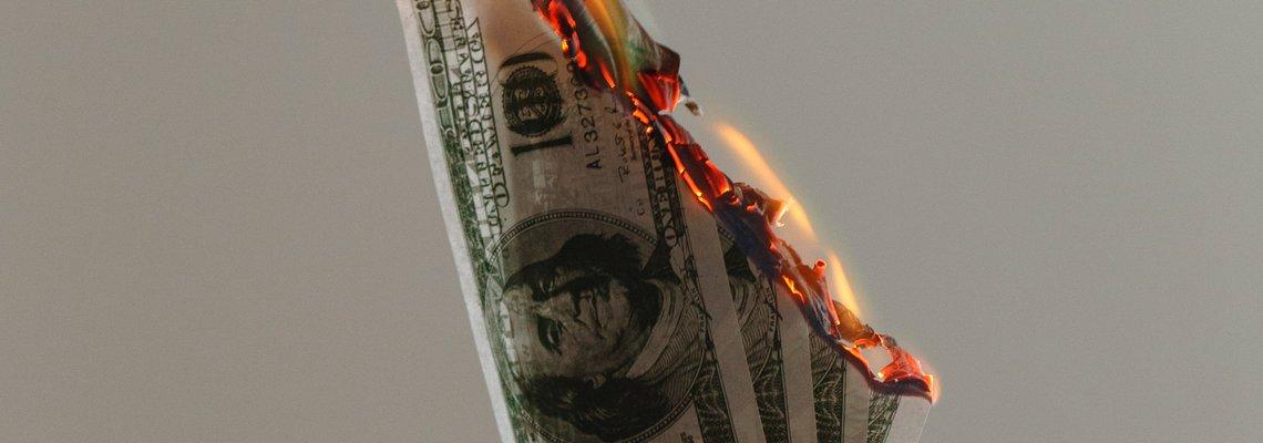 Hands Holding Money Bills on Fire