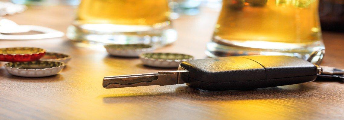 Car Keys resting near glasses of beer and beer bottle caps