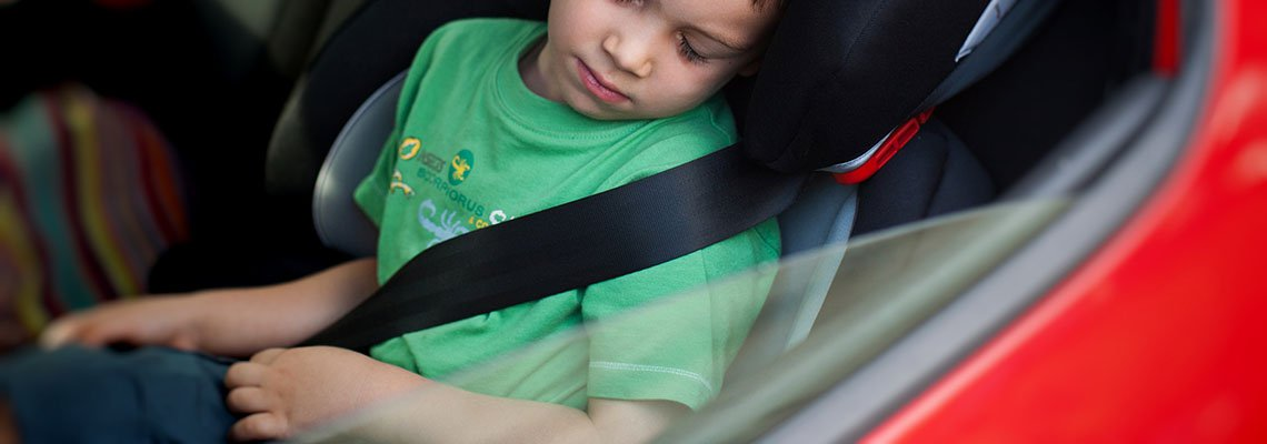 Child asleep in booster seat in the back of a car