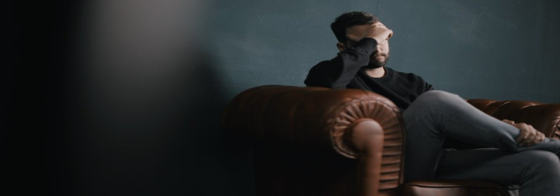 Man sitting on sofa alone with his head in his hands