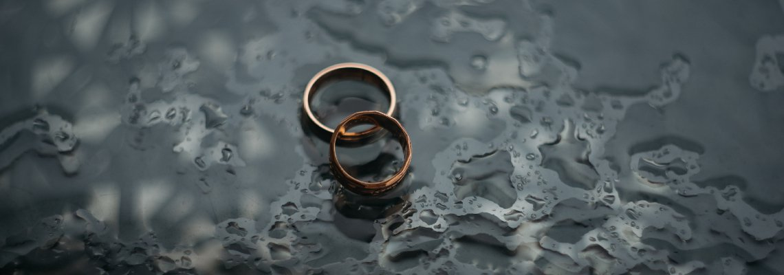 Two wedding rings sitting in a puddle of water