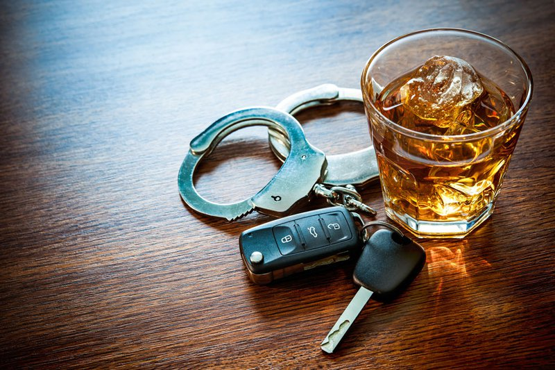 Alcoholic beverage, handcuffs and car keys on a table