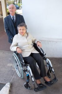 Two elderly people, one in a wheelchair and one pushing them