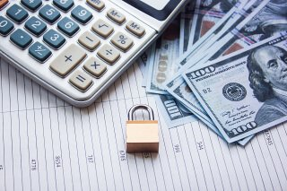 calculator padlock and one hundred dollar bills