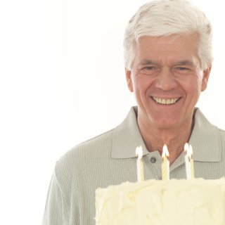 man looking at cake with candles
