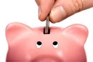 person putting a coin into a piggy bank