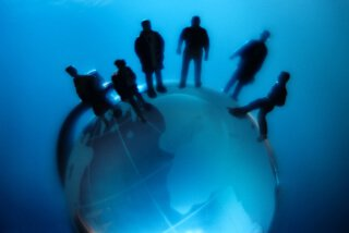 silhouettes of people standing on a globe