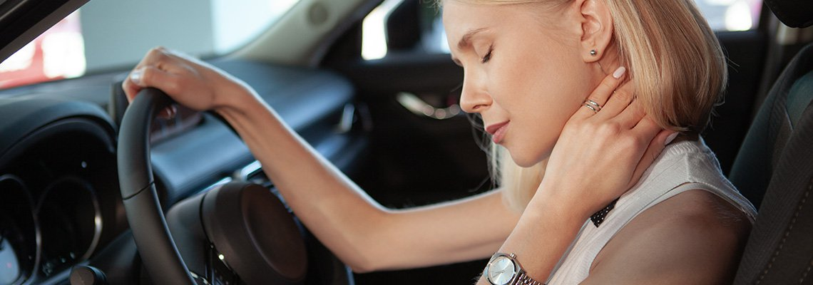 A woman holds her neck in her car