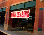 now leasing sign in front of a building