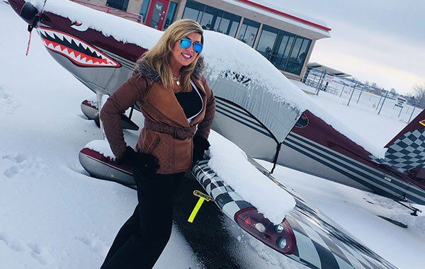 Woman in the snow with a plane