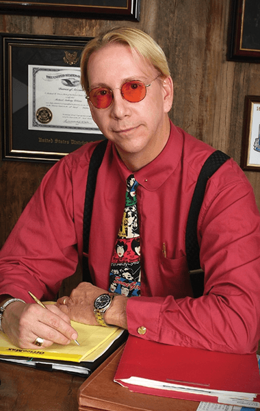 Urbano in his office with red sunglasses and red shirt